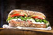 Sandwich mit Vollkornbrötchen, Salat, gekochtem Ei und Schinken