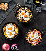 Fried potato and eggs in black round pans with adding roasted ham or black pudding in composition with bread and ingredients