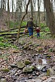 Vater mit Kind im Frühling im Laubwald