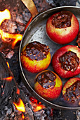 Grilling stuffed apples over a fire