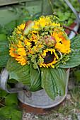 Herbststrauß aus Sonnenblumen, Fencheldolden, Birnen und Funkienblättern in Gießkanne