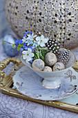 Kleine Osterdeko mit Sträußchen aus Vergißmeinnicht, Kirschblüten und Puschkinie in Sammeltasse mit Ostereiern und Federn