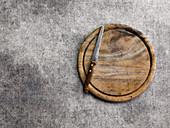 Rundes Holzschneidebrett mit Messer auf grauem Untergrund