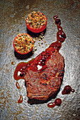 Grilled entrecôte with cranberry jus and gratinated herb tomatoes