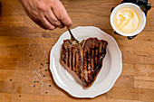 Seasoning a grilled porterhouse steak