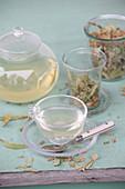 Lindenblütentee in Teefilter und aufgebrüht in Glaskanne und Tasse