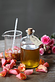 Rose oil in a glass bottle next to rose petals