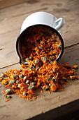 Dried marigold flowers fall from enamel jug