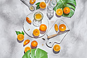 Whole and half of ripe oranges arranged on table with knife and glass with juice