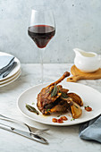 Roasted quail garnished with pears and leaves served with glass of red wine