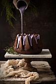Pouring blueberry glaze on chocolate Bundt cake