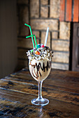 Sweet milkshake with chocolate syrup and whipped cream garnished with colorful sprinkles