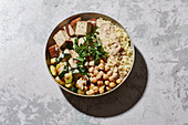An oriental bowl with couscous, chickpeas, courgette and tofu