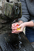 A woman washes an apple in a natural water source
