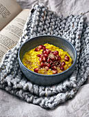 Gold rice pudding with pomegranate seeds and sesame seeds