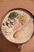 Different dried herbs on an antique wooden tray