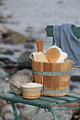 Antique sauna bucket and bathroom utensils on old wooden chair on beach