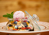 Scoop of ice cream in glass jar with various berries and garnished with sprig of mint