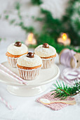 Christmas Cupcakes decorated with chocolate balls and sprinkled with coconut flakes