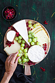 Cheese platter with sweet grapes and red currants