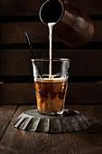 Frische Milch in Glas mit heißem Kaffee giessen