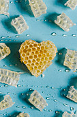 Heart shaped honeycomb with delicious honey on blue background