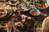 Assorted dishes of Vietnamese cuisine arranged on wooden table