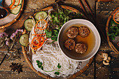 Bun Cha with meatballs and rice noodles served on plate with fresh herbs and vegetables