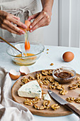 Adding eggs in glass bowl, walnuts and Blue cheesecake on wooden board