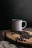 Aromatic coffee beans and metal cup of hot cappuccino