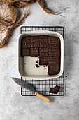 Baking pan with traditional brownie cake cut into pieces