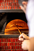 A pizza being baked in a stone oven