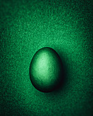 Dark green Easter egg on a dark green background