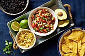 Zutaten für Chilaquiles - schwarze Bohnen, Tortillachips, Mais und Salsa