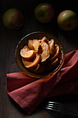 Sliced baked apples served in bowl with napkin