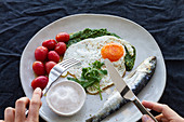 Fried egg, with salty herring, marinated tomatoes and pesto sauce