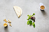 Snack ingredients – tortillas, mixed leaf salad, creamy peanut butter and fried onions