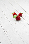 Fresh strawberries on white wooden plank surface