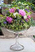 Gesteck mit Rosen, Vogelwicke, Holunderblüten und unreifen Äpfeln in Glaspokal