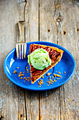 Slice of pecan nut tart with pistachio ice cream