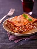 Ein Stück klassische Lasagne mit Basilikumblatt