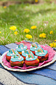A plate of colorful muffins with rainbow decorations in a meadow