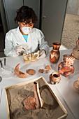 Restorer working on Moche ceramics