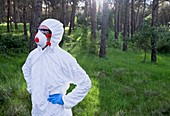 Person in protective suit in forest