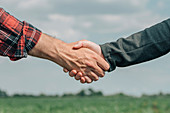 Mortgage loan officer and farmer shaking hands