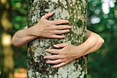 Environmentalist hugging tree