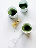 Three cups of Matcha tea with whisk