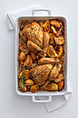 Lemon chicken with bacon, potatoes and thyme in a baking dish