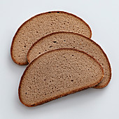 Three slices of rye bread on a white surface