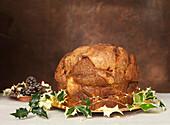 Panettone mit Ilexzweigen auf Kuchenplatte